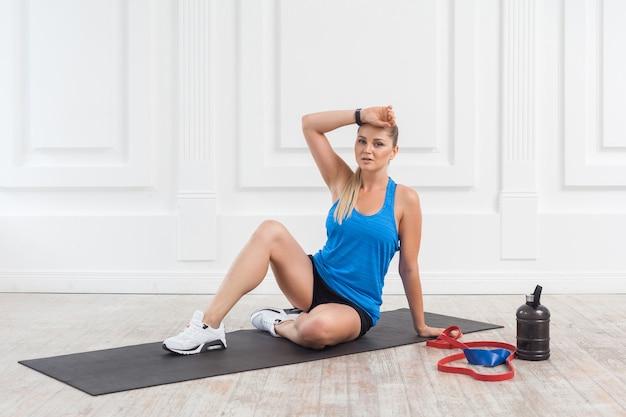 Sportowa piękna młoda wysportowana blondynka w czarnych spodenkach i niebieskim topu jest spocona i odpoczywa po ciężkiej pracy na siłowni. wewnątrz, studio strzał, koncepcja sportowa, patrząc na kamerę