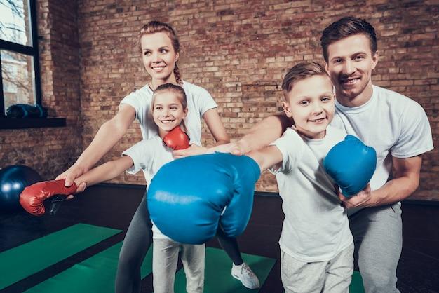 Sportowa rodzina ma trening bokserski w klubie fitness.