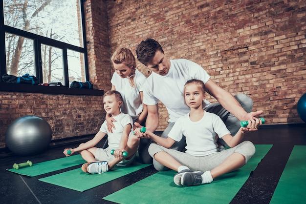 Sportowa rodzina robi ćwiczenia z hantlami.