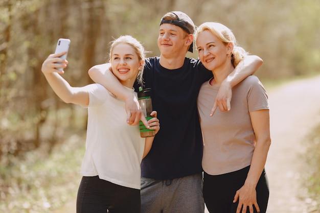 Sportowa rodzina stoi w letnim lesie