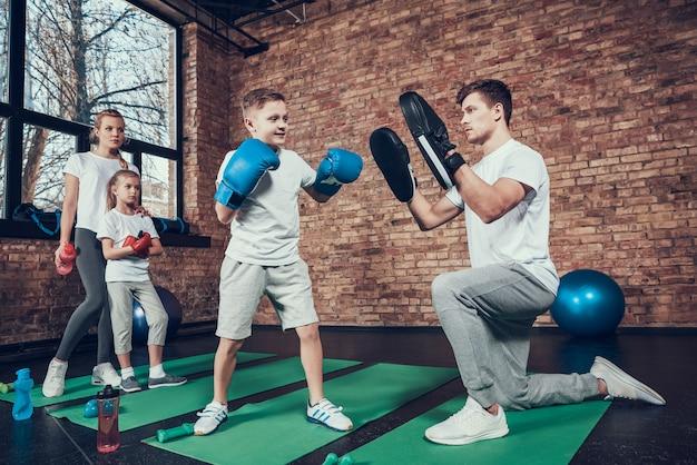 Sportowa rodzina w rękawiczkach trenuje na siłowni.