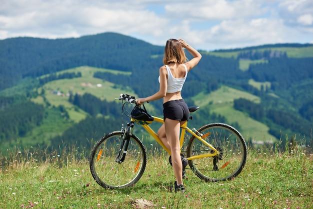 Sportowa rowerzystka z żółtym rowerem górskim