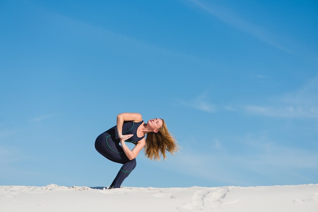 Sportowa samica robi asanę i namaste na pustyni