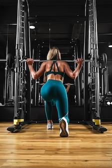 Sportowa seksowna dziewczyna trenuje nogi, wykonując ćwiczenia z dużymi ciężarami na sztangę