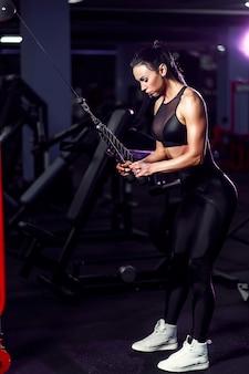 Sportowa seksowna kobieta robi ćwiczeniu używać maszynę w gym - boczny widok