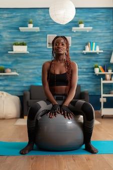 Sportowa silna czarna kobieta siedząca na piłce stabilizacyjnej