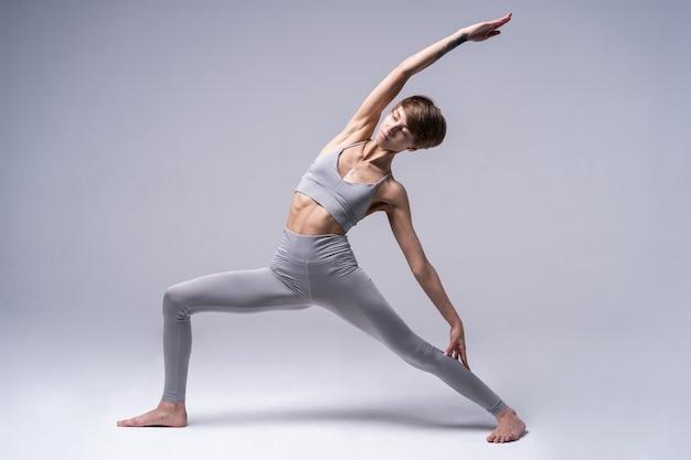 Sportowa skoncentrowana kobieta uprawiania jogi w odzieży sportowej