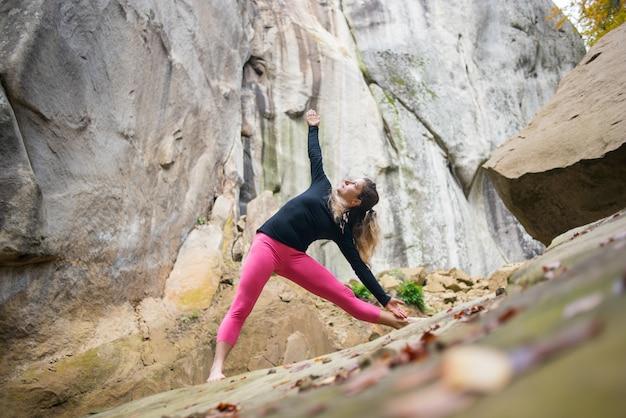 Sportowa sprawna kobieta ćwiczy jogę na głazie w naturze