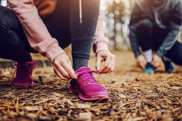 Sportowa, sprawna młoda kobieta, wiążąca sznurówki, kucając na szlaku w przyrodzie i przygotowując się do biegania.