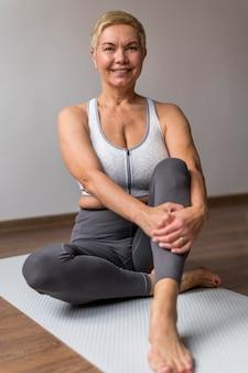 Sportowa starsza kobieta z krótkimi włosami siedzi na macie do jogi