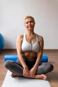 Sportowa starsza kobieta z krótkimi włosami siedzi w pozycji lotosu