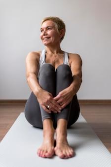 Sportowa starsza kobieta z krótkimi włosami siedzi