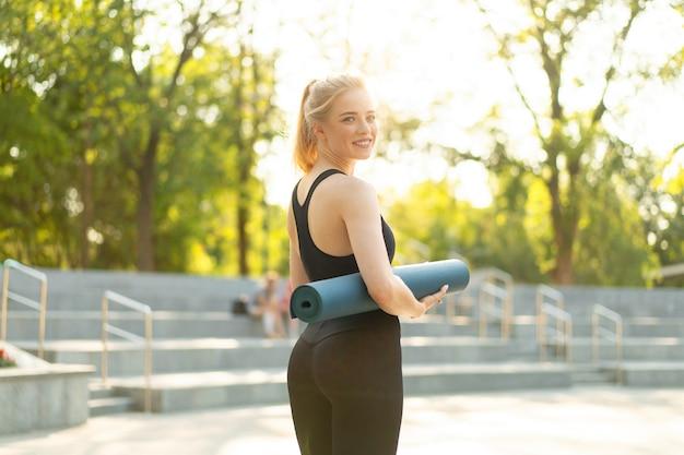 Sportowa szczupła kobieta sportowe ubrania czarne legginsy i stojący w pobliżu betonowych schodów, trzymając matę do jogi, odpoczywając między ćwiczeniami. sport and fitness concept kaukaska wysportowana kobieta idzie na trening