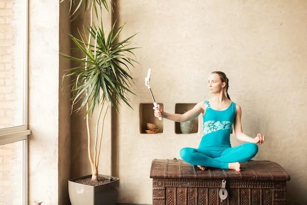 Sportowa szczupła ładna kobieta w sportowej treningu hatha joga sport onlinefitness online i koncepcja rekreacji selfie i rozmowa wideo