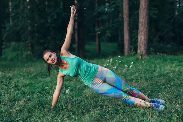 Sportowa szczupła sportsmenka robi boczny deski jogi stanowią stojący na trawie w letni poranek