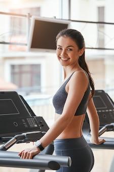 Sportowa uroda wesoła i piękna młoda kobieta w stroju sportowym stoi na bieżni na siłowni