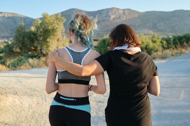 Sportowa zdrowa, aktywna rodzina, matka i nastoletnia córka chodzą w odzieży sportowej