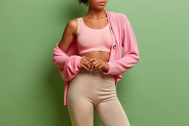 Sportowa, zdrowa, szczupła kobieta nosi topowe legginsy i sweter ma miękką skórę, która jest w dobrej kondycji i zadbane ciało.