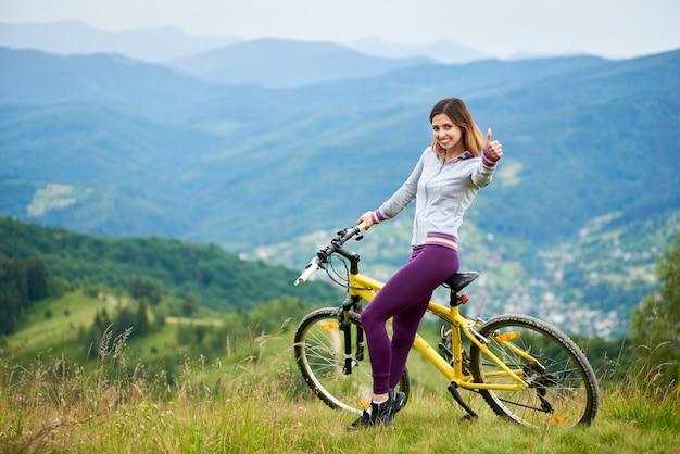 Sportowa żeńska rowerzysta pozycja z żółtym rowerem górskim na górze góry