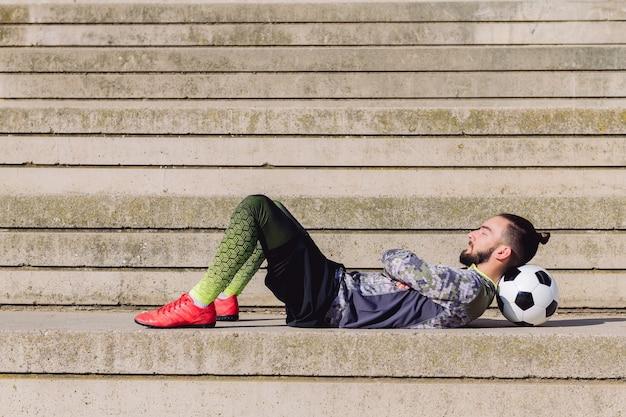 Sportowca leżącego na betonowym boisku do piłki nożnej