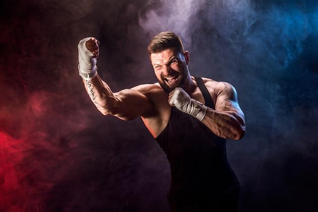 Sportowca muay thai bokser walki na czarnej ścianie z dymem.