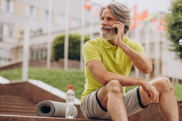 Sportowca w średnim wieku siedzi na schodach przy użyciu telefonu