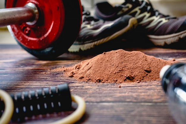 Sportowcy muszą spożywać dodatkowe białko w proszku, na obrazie o smaku kakao, aby poprawić swoje wyniki sportowe.