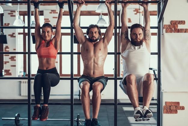 Sportowcy powiesić na poziomym pasku z utopione nogi.