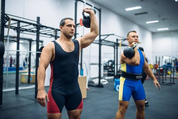 Sportowcy z ciężarami na siłowni, podnoszenie kettlebell