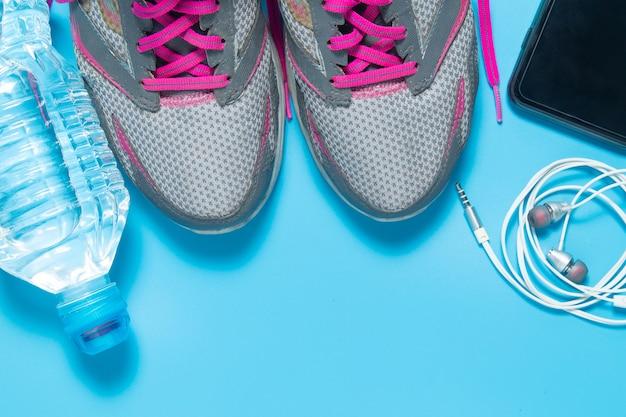Sportowe buty płaskie z bidonem, smartfonem, słuchawkami.