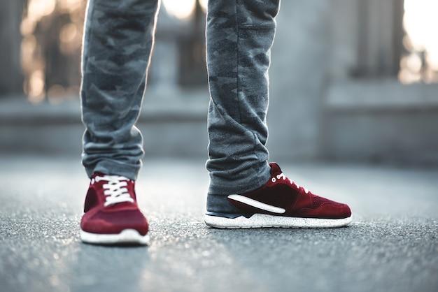 Sportowe czerwone trampki z bliska na asfalcie. nogi i buty z niższego kąta.