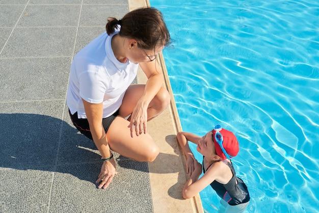 Sportowe dziecko dziewczynka w okularach sportowych czapka strój kąpielowy w odkrytym basenie rozmawia z trenerem kobieta