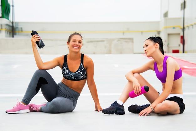 Sportowe dziewczyny ćwiczące i nawilżające na świeżym powietrzu