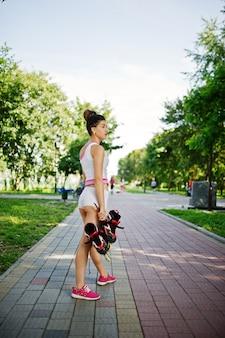 Sportowe dziewczyny noszą białe spodenki i koszulę z rolkami w parku.