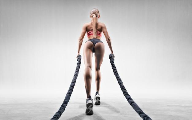 Sportowe dziewczyny pociągi z linami. widok z tyłu.