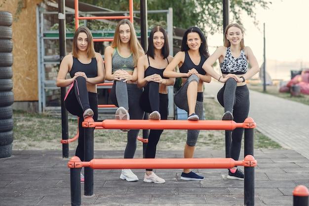 Sportowe dziewczyny trenujące w letnim parku