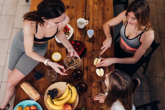 Sportowe dziewczyny w kuchni, gotowanie łatwych posiłków.