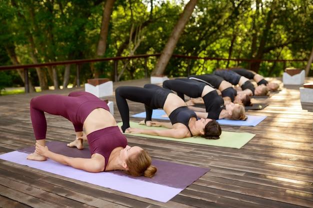 Sportowe kobiety na grupowym treningu jogi w parku latem