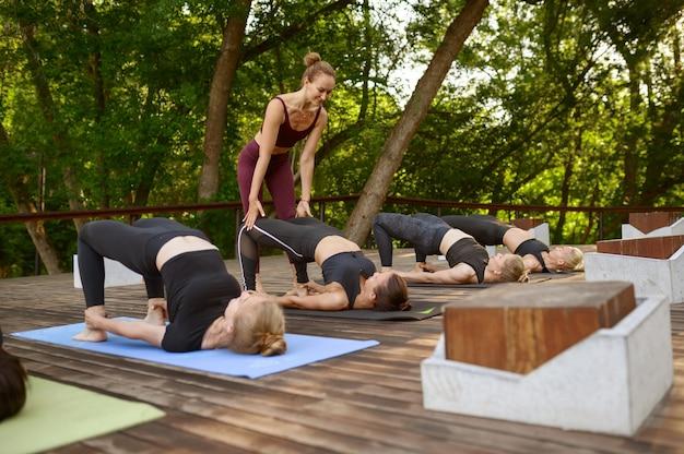 Sportowe kobiety na grupowym treningu jogi z instruktorem w letnim parku