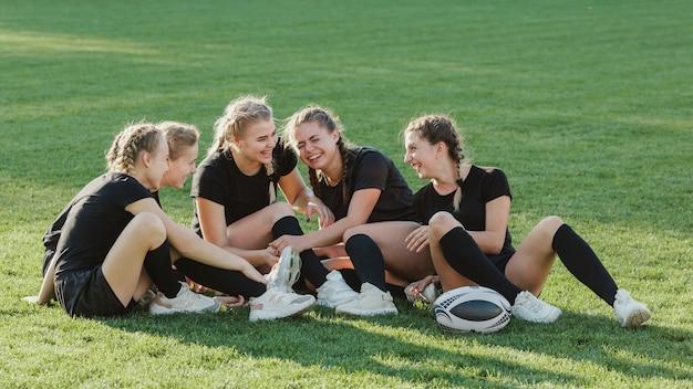 Sportowe kobiety rozmawiają ze sobą na trawie