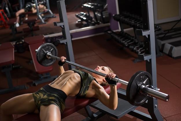 Sportowe młoda kobieta robi ćwiczenia ze sztangą na ławce w siłowni. wyciskanie na ławce barowej.