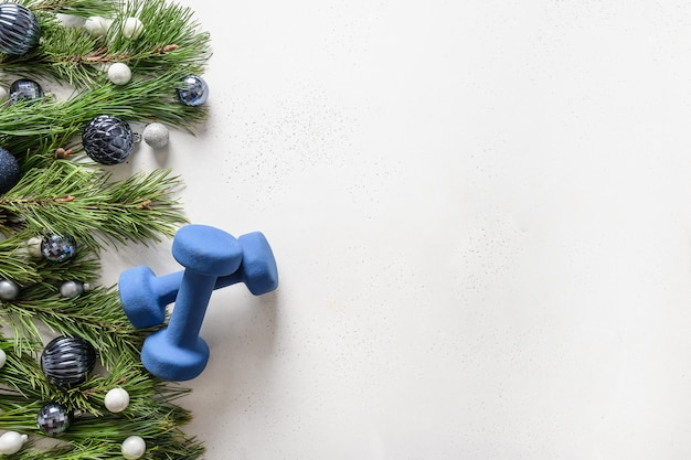 Sportowe ramki świąteczne z niebieskimi hantlami, świąteczne bombki na białym tle. kartka z życzeniami.