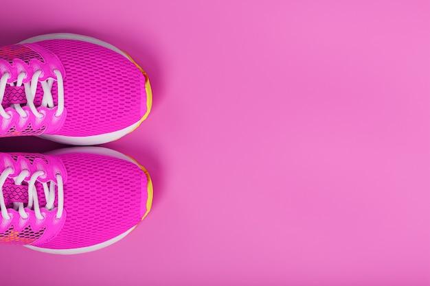 Sportowe różowe trampki na różowym tle