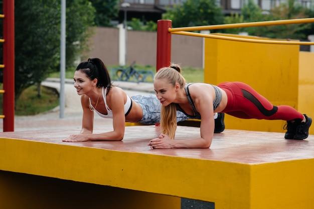 Sportowe, seksowne dziewczyny stoją w barze na świeżym powietrzu. fitness, zdrowy styl życia