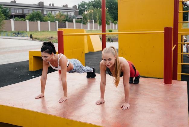 Sportowe, seksowne dziewczyny synchronizują push-ups na zewnątrz. fitness, zdrowy styl życia
