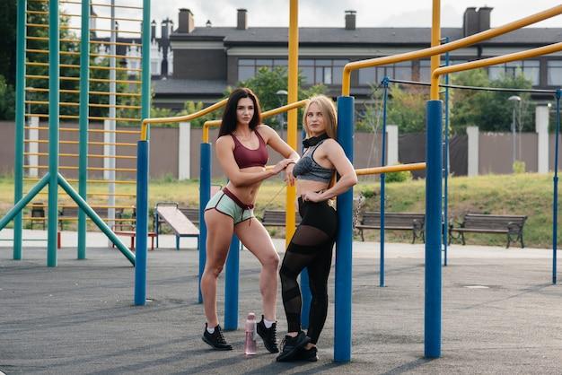 Sportowe, seksowne dziewczyny uprawiają sport na świeżym powietrzu. fitness, zdrowy styl życia