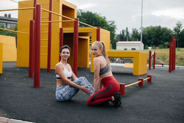 Sportowe, seksowne dziewczyny wykonują ćwiczenia abs na świeżym powietrzu. fitness, zdrowy styl życia