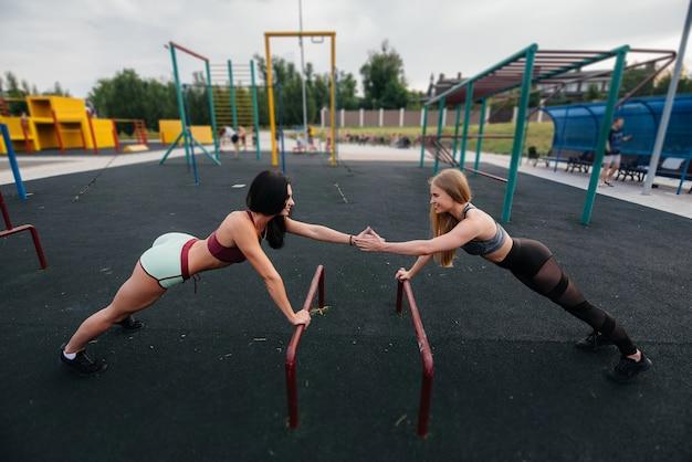 Sportowe, seksowne dziewczyny wykonują push-ups na zewnątrz. fitness, zdrowy styl życia