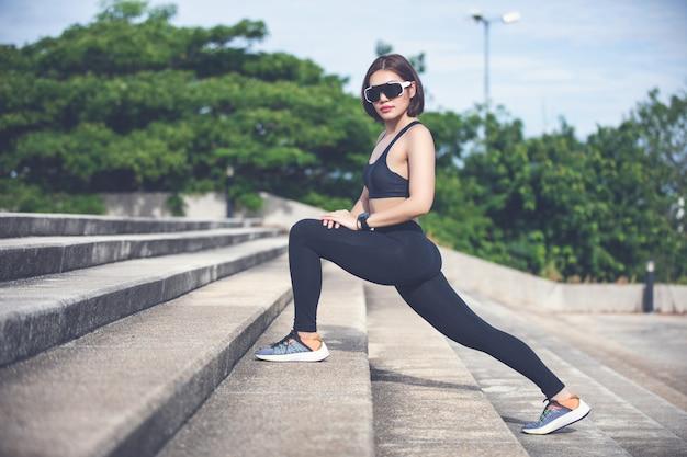Sportowej kobiety azjatykci rozgrzewkowy up i młoda żeńskiej atlety obsiadanie na ćwiczyć i rozciągać w parku przed biegaczem outdoors, zdrowy styl życia