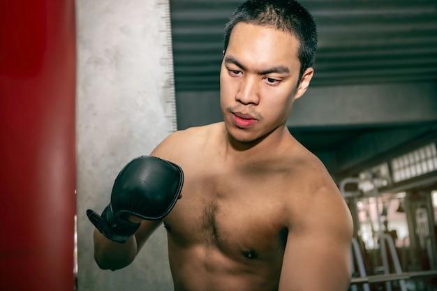 Sportowiec azjatycki mężczyzna bokser trening na worek treningowy na siłowni fitness